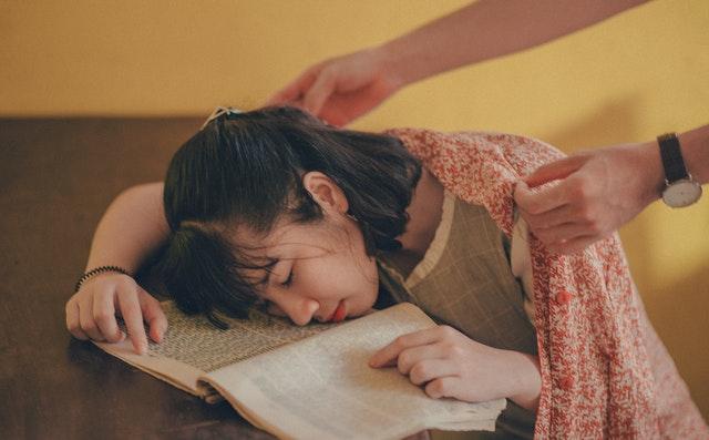 žena spiaca nad knihou