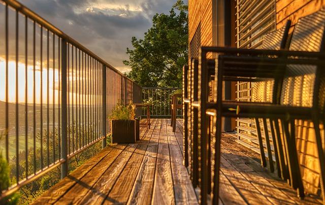 Balkón so zábradlím, na ktorom sú stoličky, počas západu slnka.jpg